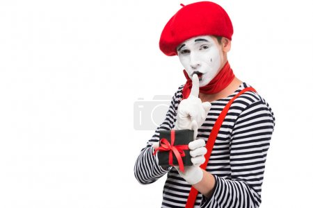 mime holding present box and showing silence gesture isolated on white