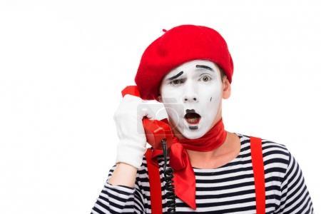 Photo pour Mime choqué parler par téléphone fixe isolé sur blanc - image libre de droit