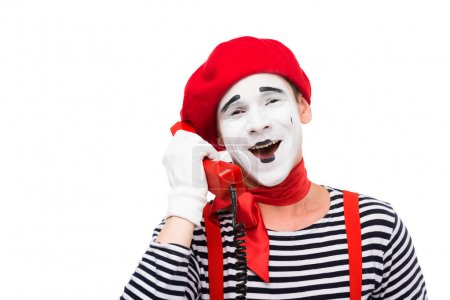 smiling mime talking by stationary telephone isolated on white
