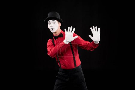 mime showing stop sign isolated on black