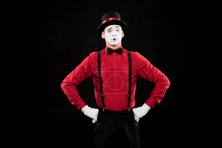 grimacing mime standing with hands akimbo isolated on black