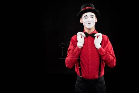 happy mime fixing bow tie isolated on black
