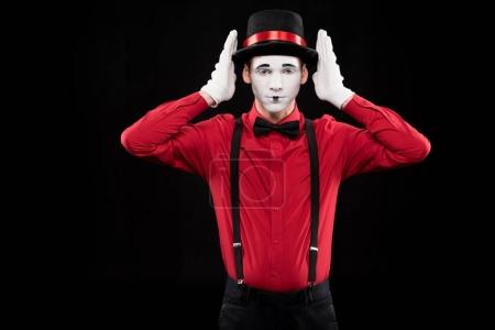 mime covering ears with hands isolated on black