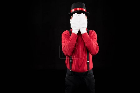 mime covering face with hands isolated on black