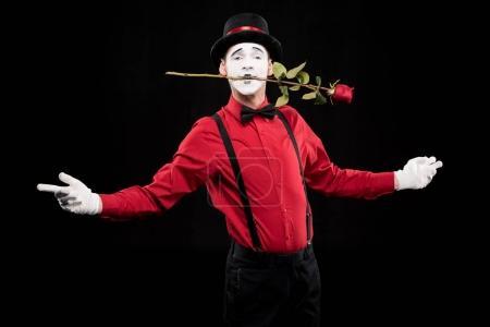 Photo pour MIME tenant une rose rouge dans la bouche et debout avec les bras ouverts isolées sur fond noir - image libre de droit