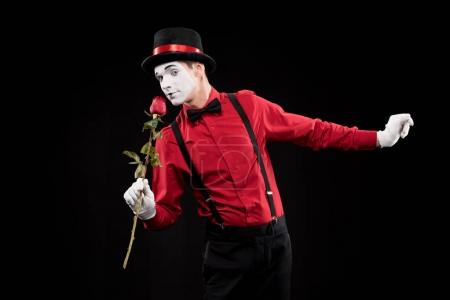 Photo for Mime sniffing red rose isolated on black - Royalty Free Image