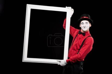 Photo for Smiling mime holding frame isolated on black - Royalty Free Image