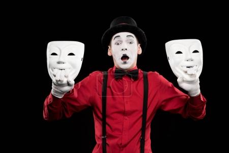 Photo for Shocked mime holding two masks isolated on black - Royalty Free Image