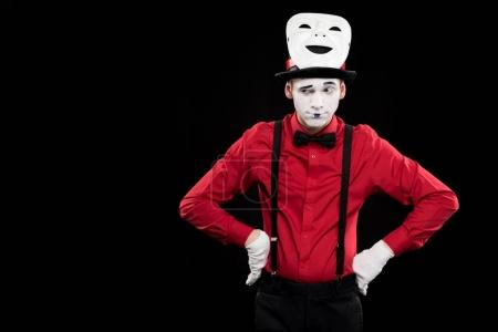 grimacing mime with hands akimbo and mask on hat isolated on black
