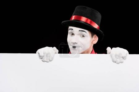 Photo for Happy mime looking out from empty board isolated on black - Royalty Free Image