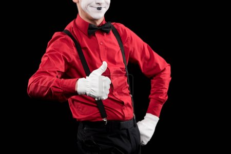 cropped image of mime showing thumb up isolated on black