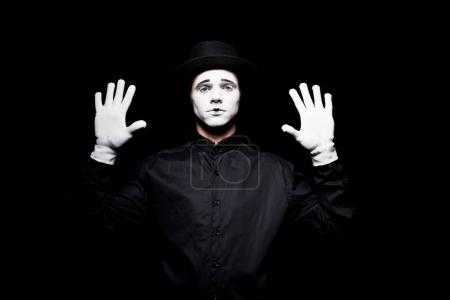 mime pretending touching something with hands isolated on black