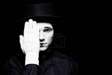 Photo for Mime covering eye and looking at camera isolated on black - Royalty Free Image