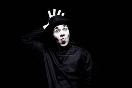 mime sticking tongue out and grimacing isolated on black
