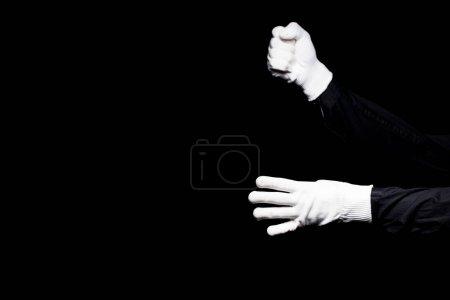 Photo pour Image recadrée de mime faisant semblant d'escalader une corde isolée sur noir - image libre de droit