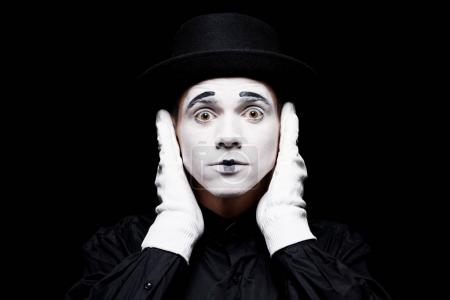 mime covering ears and looking at camera isolated on black