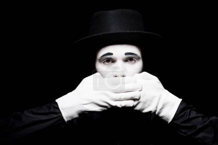 Photo for Mime covering mouth and looking at camera isolated on black - Royalty Free Image