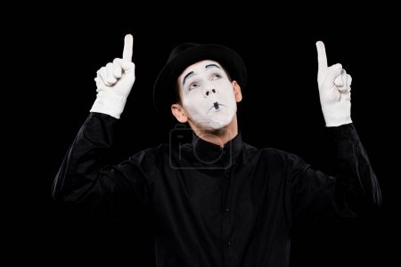 Photo for Grimacing mime pointing on something isolated on black - Royalty Free Image