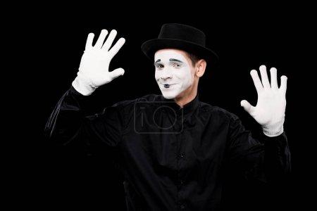 Photo pour Sourire mime effectuer et toucher quelque chose isolé sur noir - image libre de droit