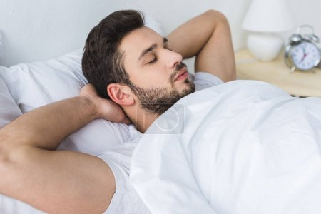 bearded man relaxing on bed in bedroom