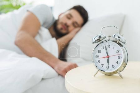 Photo for Alarm clock on table, man sleeping in bed on background - Royalty Free Image