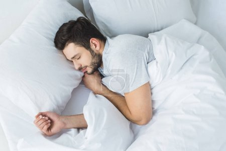 top view of bearded man sleeping on bed in bedroom