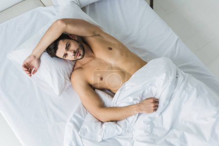 Photo pour Vue de dessus de bel homme sexy torse nu couché sur lit blanc - image libre de droit