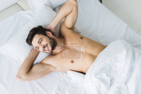 Photo for Top view of smiling shirtless man lying on white bed in the morning - Royalty Free Image