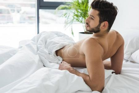 Photo for Bearded shirtless man lying on white bed in the morning - Royalty Free Image