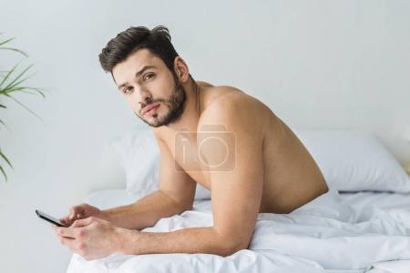 Photo pour Beau homme torse nu messagerie sur smartphone dans le lit le matin - image libre de droit