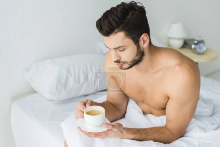 handsome bearded man holding coffee cup in bed in the morning