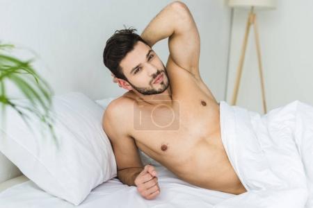 Photo pour Bel homme torse nu se détendre dans un lit blanc - image libre de droit