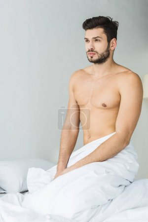 handsome bearded shirtless man sitting on white bed