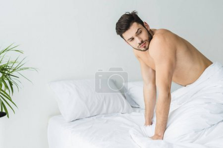 handsome shirtless man posing on white bed in the morning