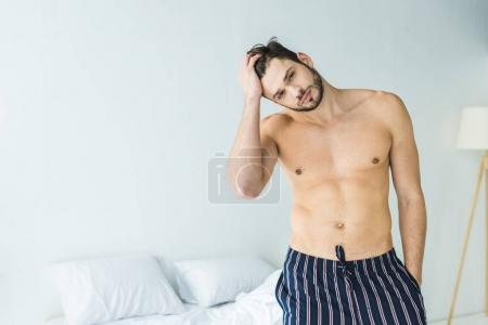 Photo for Handsome shirtless man posing in bedroom in the morning - Royalty Free Image