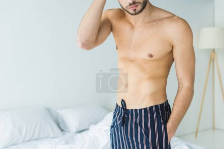 cropped view of shirtless man standing in bedroom in the morning