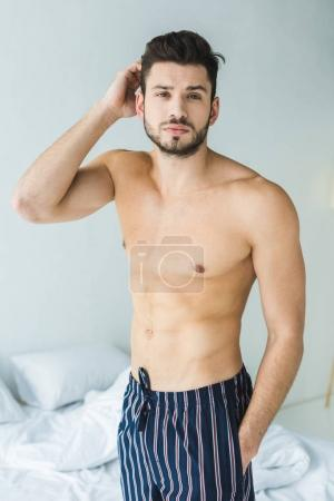 handsome shirtless man standing in bedroom in the morning