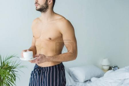 Photo for Cropped view of shirtless man standing in bedroom with cup of coffee - Royalty Free Image