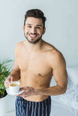 happy shirtless man standing in bedroom with cup of coffee