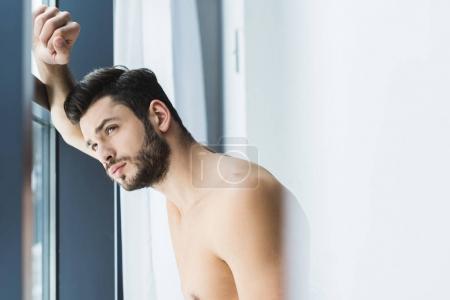 Photo pour Cher beau torse nu homme regardant la fenêtre - image libre de droit