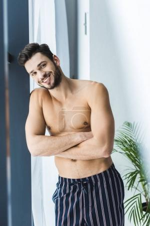 cheerful shirtless man standing at window