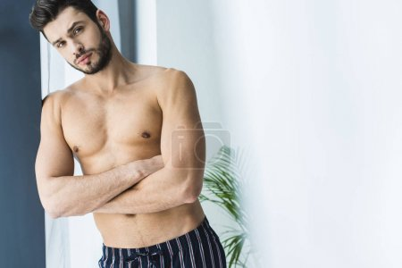 handsome shirtless man standing at window and looking at camera