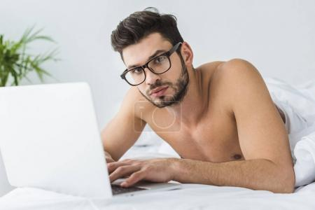 handsome man in glasses using laptop in bed in the morning