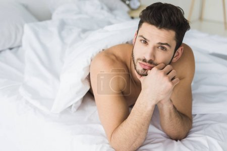 handsome thoughtful man lying on bed and looking at camera