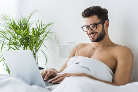 handsome smiling man using laptop in bed