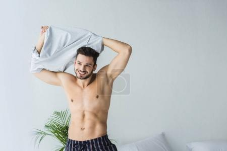 handsome sexy smiling man taking off his t-shirt in bedroom