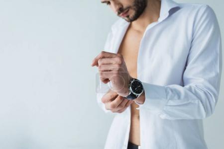 Photo pour Bel homme en chemise blanche portant la montre-bracelet, isolé sur fond gris - image libre de droit