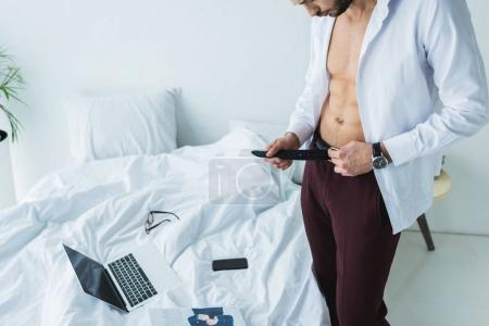Photo for Businessman wearing belt near bed with digital devices - Royalty Free Image