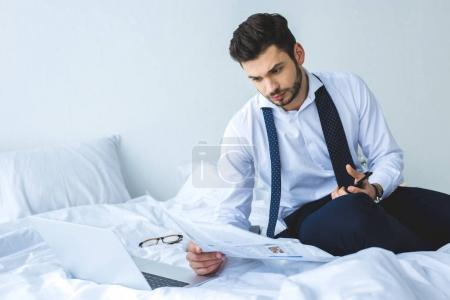 handsome businessman reading newspaper on bed with laptop