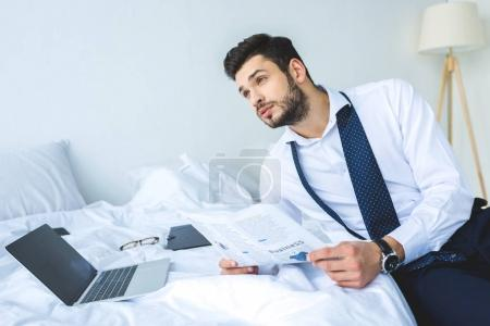 thoughtful businessman working with newspaper and laptop on bed in morning